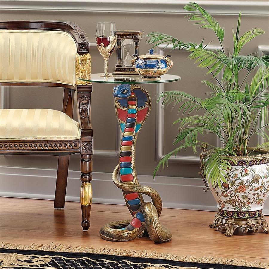 حتى الطاولات الصغيرة في هذا الاتجاه من النمط تبدو ضخمة ومشرقة. قاعدة الأثاث صلبة وضخمة. يمكن أن يكون سطح الطاولة أيًا ، بما في ذلك الزجاج ، ولكن على الرغم من الإضاءة المرئية ، إلا أنه مدعوم بأشكال يمكن التعرف عليها من الكلاب المصرية أو أبو الهول. 1